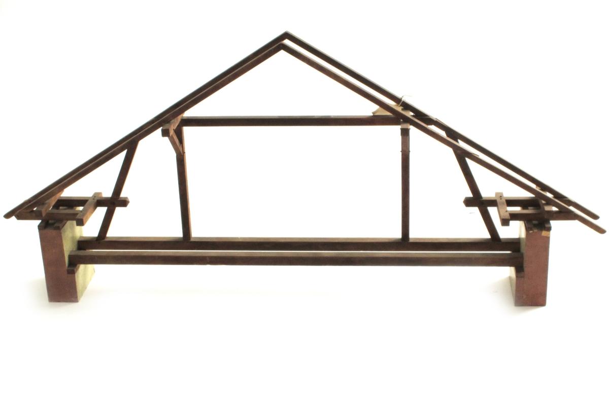 Konstruksjonsmodel  til undervisning på yrkesskole. Modell som viser tverrsnitt i takkonstruksjonen i hus med murvegger. Bjelkene på tvers av rommet ligger på avsatser i murveggen. Taket er avstivet med skråstivere.