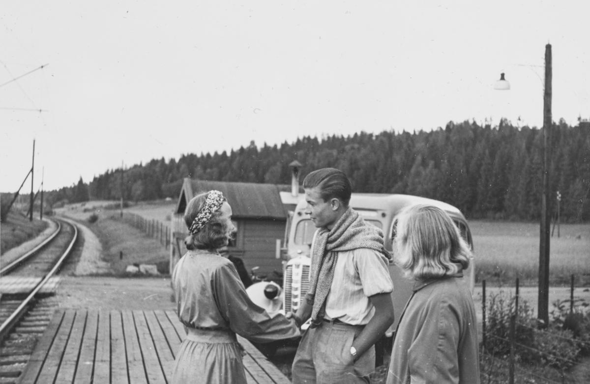 """Venter på toget på Sonsveien holdeplass.   Tekst fra album: """"På gjensyn i byen!. Gro og Chris ved førstnevntes avreise 26/7-1940 kl. 16.24."""""""
