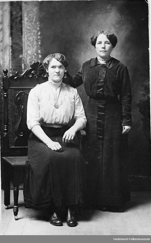 Portrett , helfigur av to unge kvinner. Stående i mørk kjole er Ragna Slåtthagen. Sittende i mørkt kjørt og lys bluse er ei venninne av Ragna.