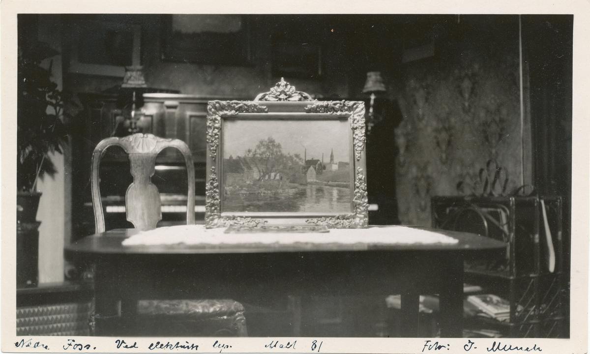 """Fotografi av oljemaleriet """"Nedre foss"""" av Edvard Munch (innrammet, stående på bord)."""