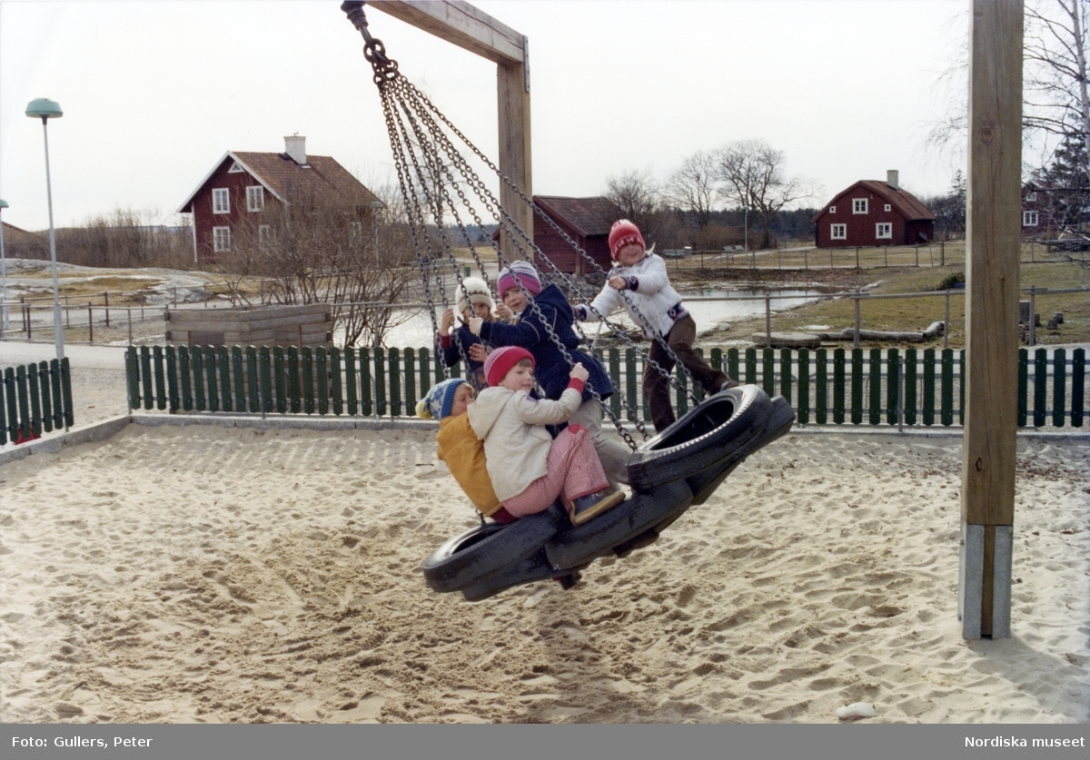 Barn gungar i bildäcksgunga på en lekplats i Akalla by.