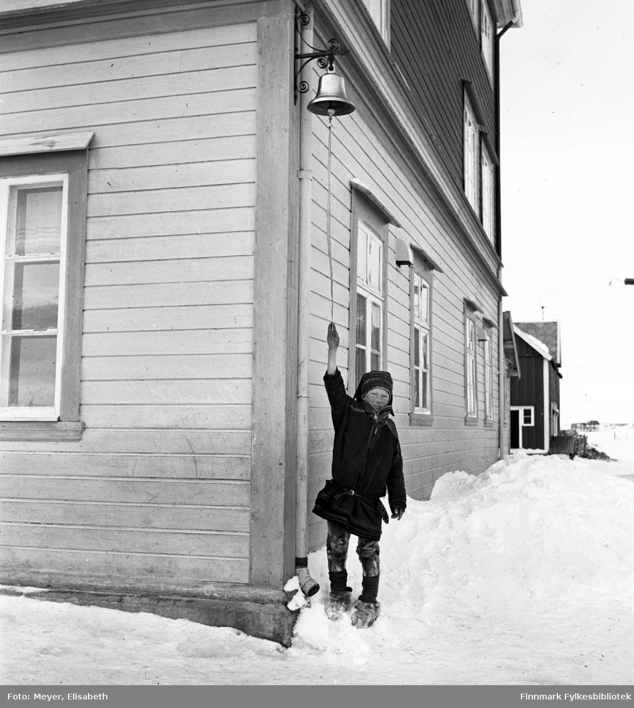 """Skolegutt ringer med skoleklokka utenfor Kautokeino skoleinternat. Skoleinternatet brant ned i 1944 under tyskernes """"Brente jords taktikk."""""""