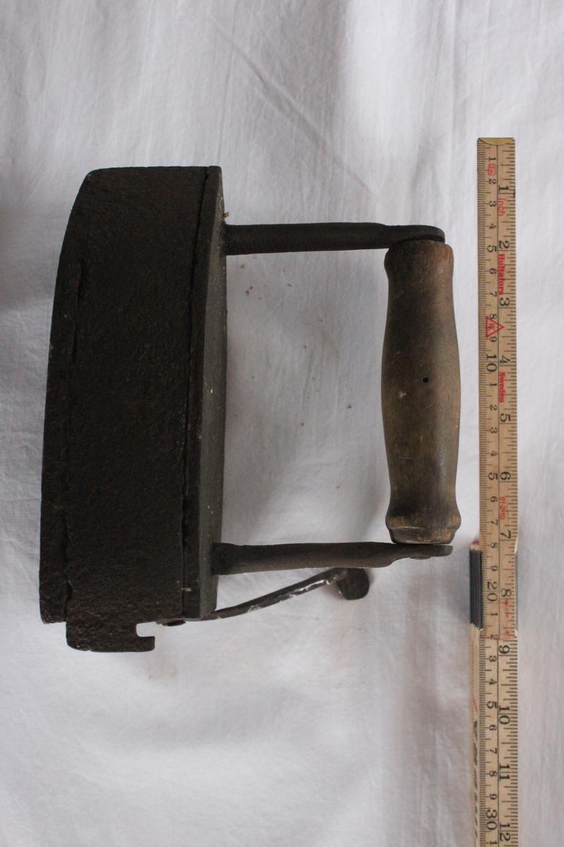 Lodstrykjärn i järn, spetsigt fram och tvärt avhugget bak. Äldre modell, med svänglucka och lod. Hakeförsedd lucka fäst i ena bakkanten med sprint. Två ståndare med svarvat trähandtag mellan.
