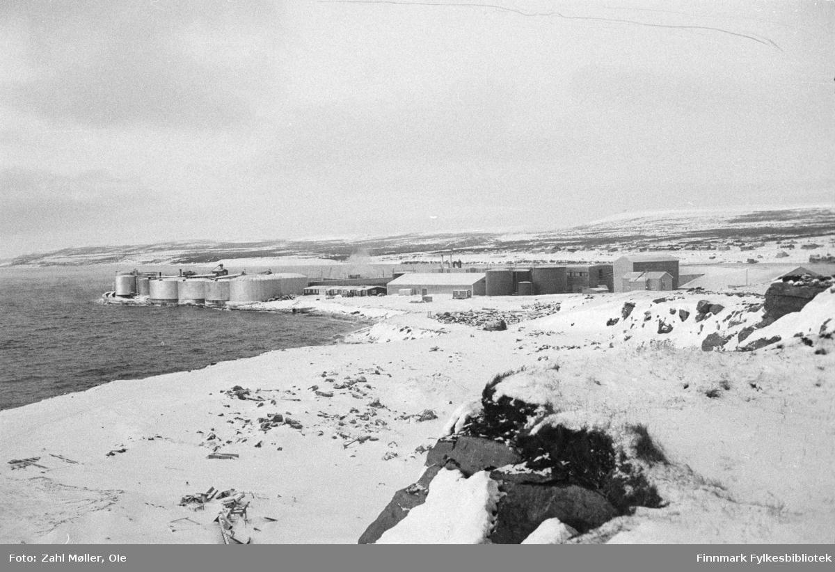 Vadsø 1968-69. Dette vinterbildet er tatt ute på Vadsøya i 1968. Bildet viser Vadsø sildoljefabrikk som ble etablert i 1953 og hadde sitt siste produksjonsår i 2009. Sildoljefabrikken var frem til slutten av 1900-tallet den desidert største industriplassen i Vadsø.