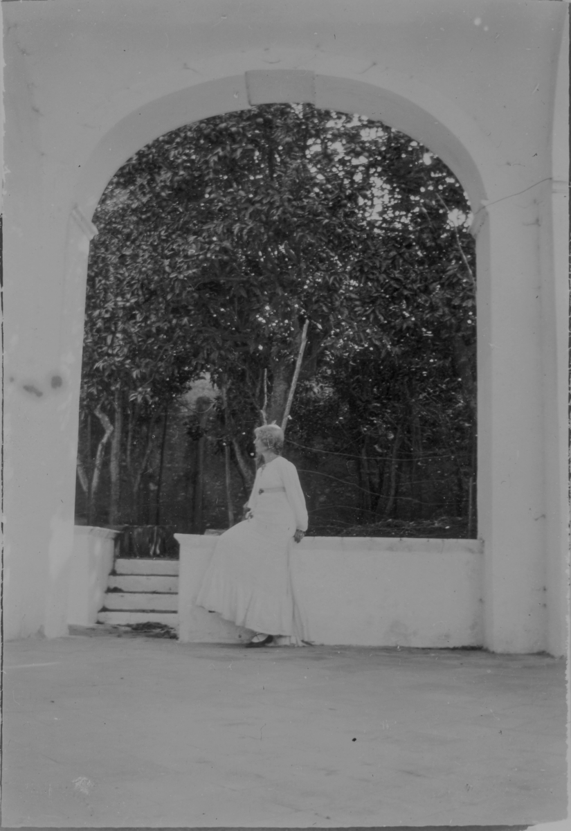 Ester Ellqvist-Bauer sitter i ett valv på deras loggia, vid huset på Capri i Italien, med utsikt över en apelsinlund. Till höger finns ytterligare tre valv.