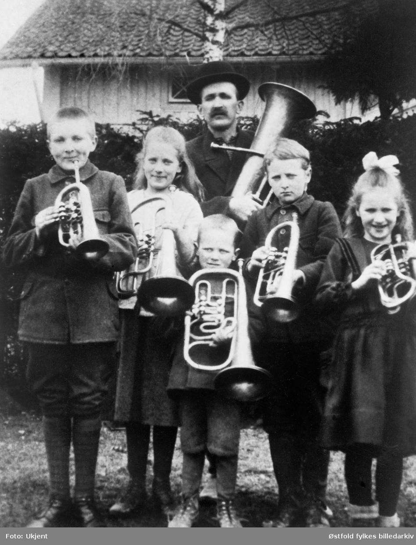 Grini Barnemusikk i Spydeberg 1918. Engebret Grini med fem av sine barn.   Engebret Grini (var jernbanearbeider og skomaker)  med fem av sine barn. Fra venstre: Anders, Signe, Engebrett, Tore, Osvald og Hjørdis - alle Grini.