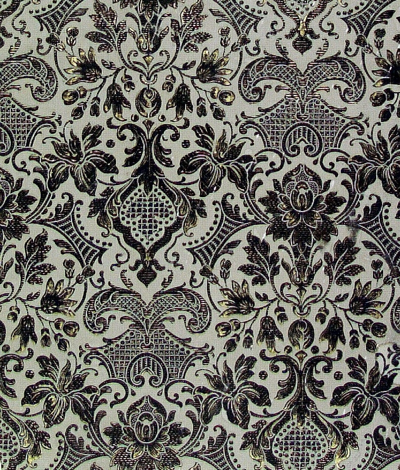 Halvnaturalistiska blommor och bladverk med fantasifullt dekorerade rocailler i diagonalupprepning. Tryck i mörkgrönt och guld på en ljusgrå bakgrund.     Tillägg historik: Tapet från en gammal gård som i slutet av 1800-talet hade namnet Sven-Anners. Tapeten har suttit direkt på timmervägg med papp under i ett stort rum med breda golv- och takplank. Rummet hade öppen spis.
