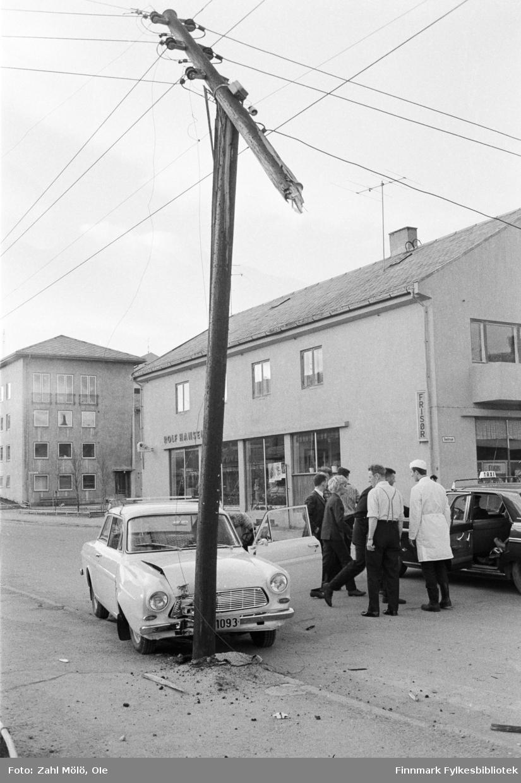 Fotoserie av fotograf Ole Zahl Mölö. Trafikkulykke i Vadsø, 1968.  En Ford Taunus 12M (1963-65) har kjørt inn i en lyktestolpe og folk har samlet seg på gata og diskuterer hendelsen.   Ole Zahl Mölö, også kjent som Zahl Møller under hans tid i Vadsø – med kunstnernavnet OZAM – er født 8.juli i 1937, i Vadsø. Fotoarkivet har ca. 7500 negativer av Ole Zahl Mölös arbeider i sin samling. Bildematerialet inneholder motiv fra Vadsøs lokalmiljø og gjenspeiler hans hverdagsliv i byen og bymiljøet i vekst på 1960-70-tallet.