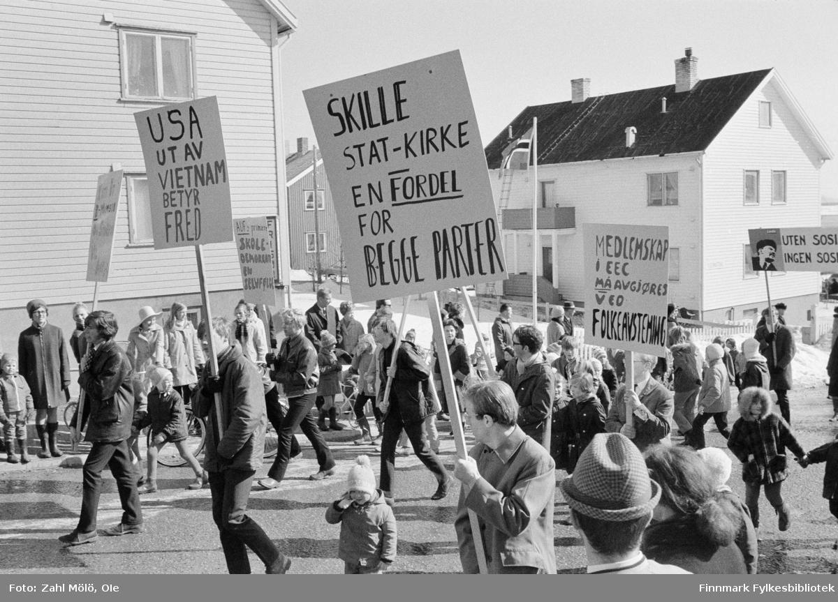 Fotoserie av fotograf Ole Zahl Mölö. Demonstrasjon i Vadsø, 1968.  EEC, Usa ut av Vietnam, Folkeavstemming. Ole Zahl Mölö, også kjent som Zahl Møller under hans tid i Vadsø – med kunstnernavnet OZAM – er født 8.juli i 1937, i Vadsø. Fotoarkivet har ca. 7500 negativer av Ole Zahl Mölös arbeider i sin samling. Bildematerialet inneholder motiv fra Vadsøs lokalmiljø og gjenspeiler hans hverdagsliv i byen og bymiljøet i vekst på 1960-70-tallet.