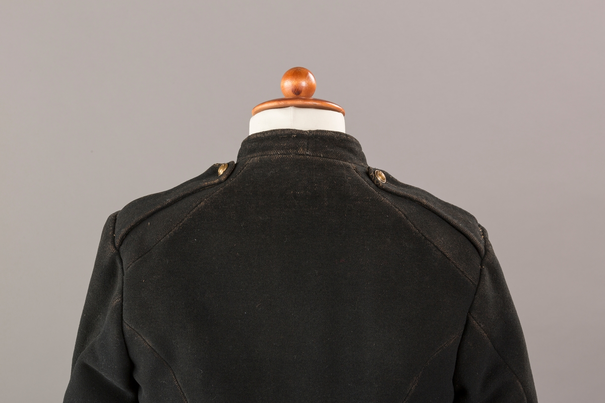 Form: Enkeltspent.  Foret med lin. Forsterket med silke på et lite stykke på ryggen. 12 messingknapper med mønster og tallet 1. Hempe i lin. Bendelbånd med knappehull.