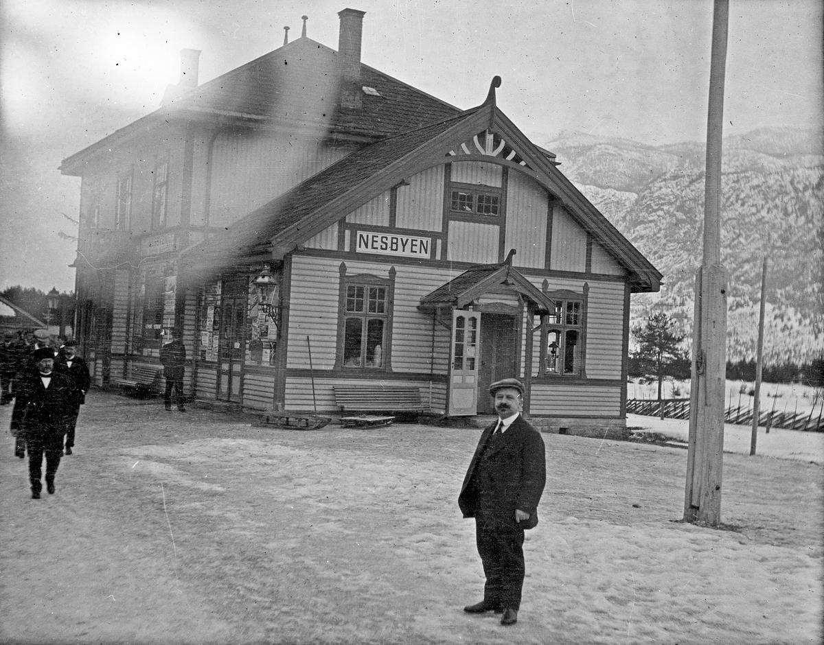 Vinterlandskap. Nesbyen stasjon. Flere personer venter utenfor. Snø på bakken. Fjell i bakgrunnen.