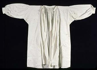 Stripade rynkor runt halskant och manschetter. Förkortad nedtill under senare tid.    Neg.nr: 1984-05