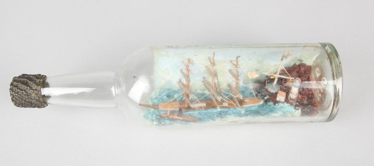 """Flaskeskip - en fullrigget seilskute i flaske. Fyrtårn og signalmast """" på land"""". Skipet fører Daneborg m. splitt, slepebåt v. bb. baug."""