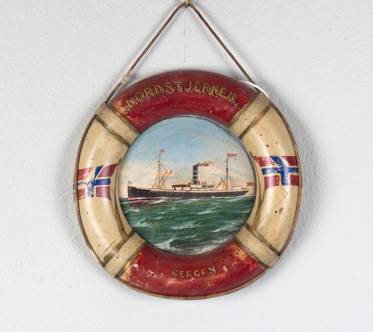 Skipsportrett av DS NORDSTJERNEN i rom sjø. Rammen er utformet som en livbøye, dekorert med norske flagg og skipets navn og hjemmehavn.