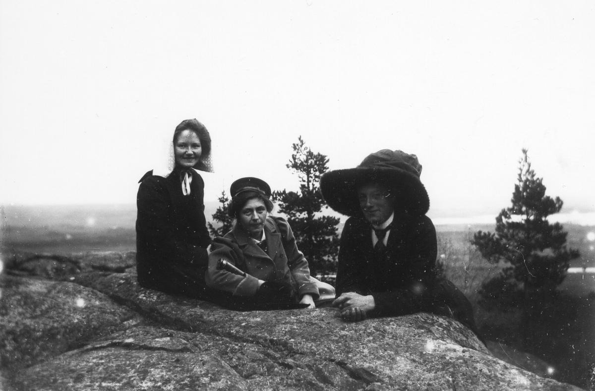 Tre kvinnor på högt belägen berghäll.