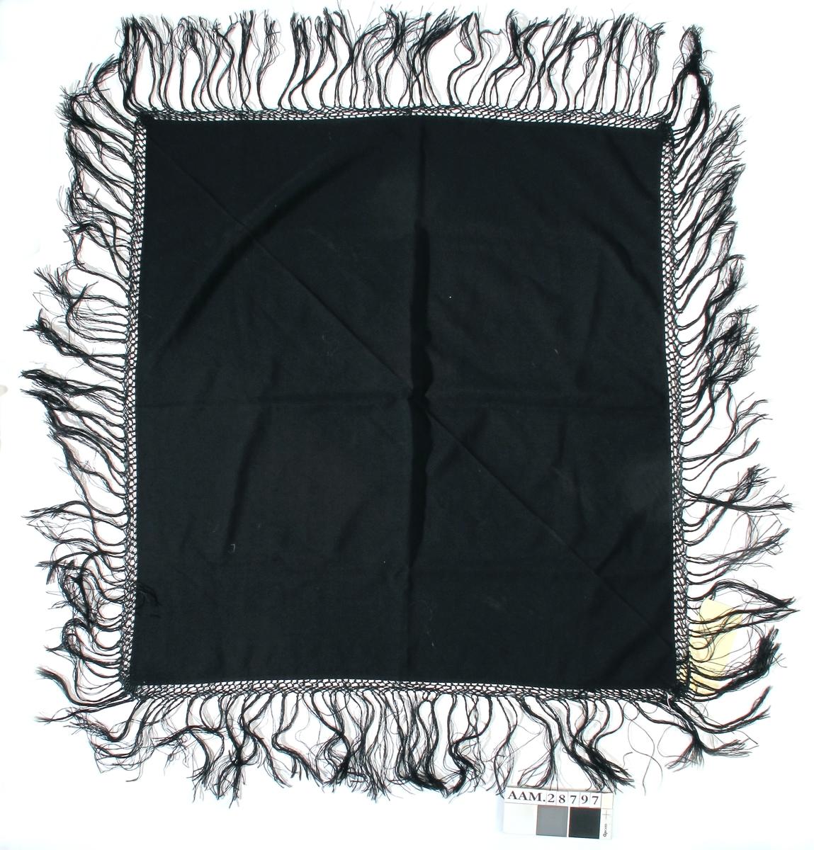 Sort sjal med frynser på fire sider. Trolig bomull tøy og silke frynser. Svært god stand.