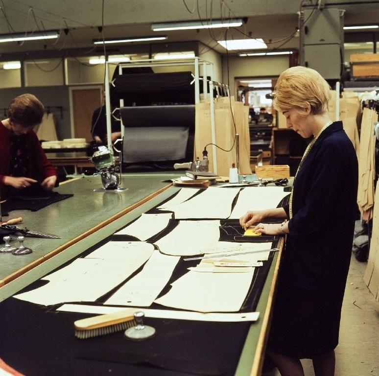 Ansatt i konfeksjonsfabrikken til Jonas Øglænd Sandnes påtegner mønster-sjablonger på stoffet før tilskjæring.