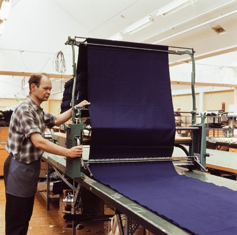 Martin Kristian Holmen, en ansatt i konfeksjonsfabrikken til Jonas Øglænd Sandnes legger opp stoff for tilskjæring med oppleggsmaskin.