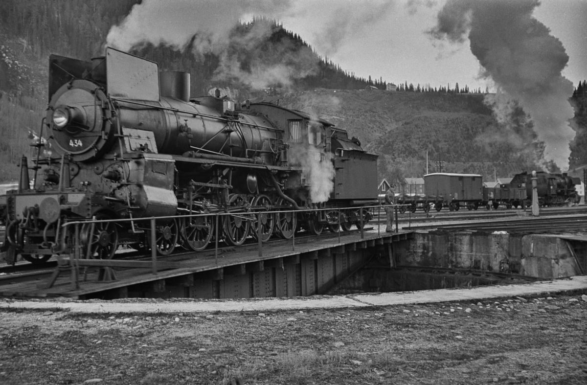 Damplokomotiv type 26c nr. 434 på svingskiven på Støren stasjon. I bakgrunnen sees godstog til Rørosbanen, trukket av damplokomotiv type 63a nr. 2343.