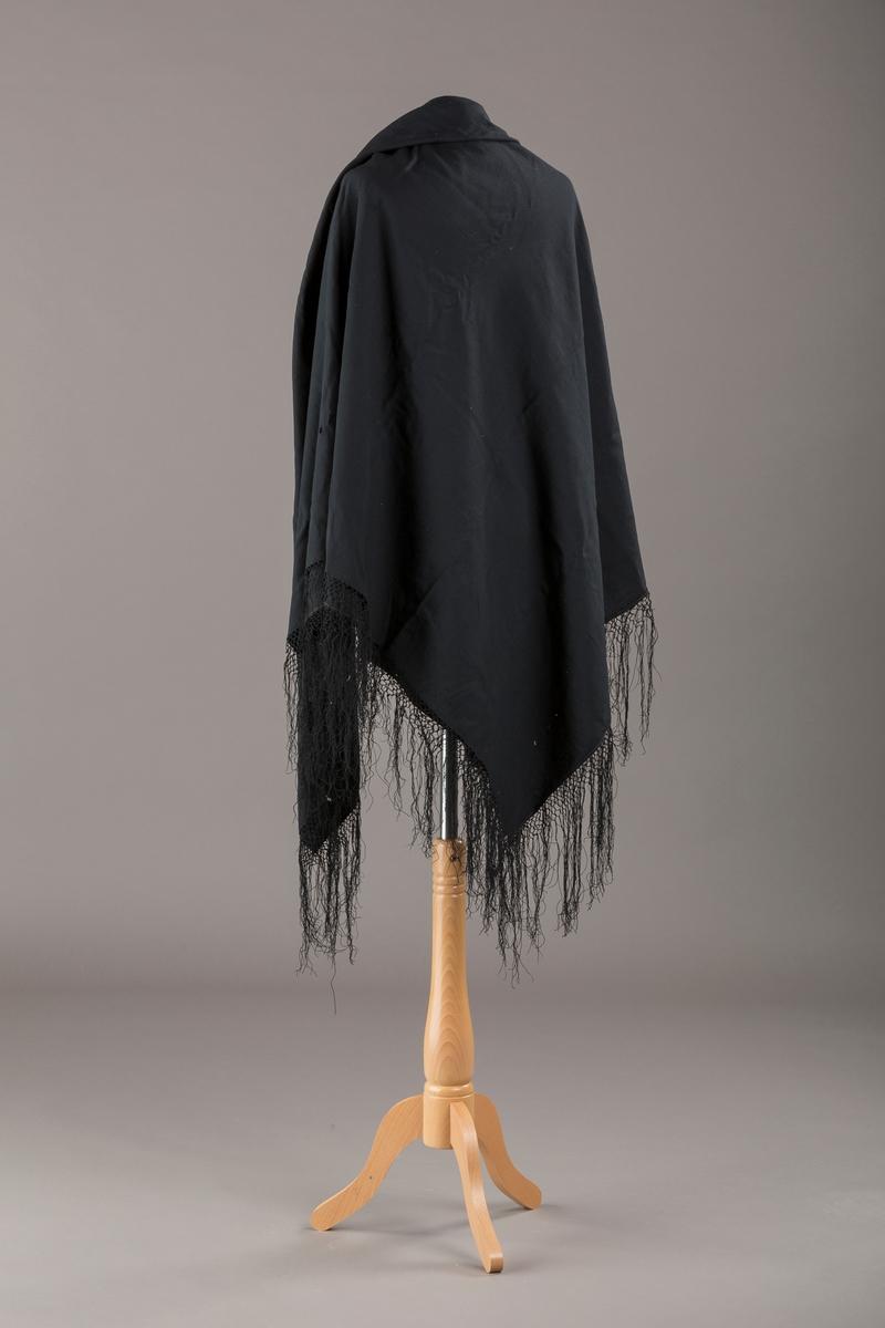 Svart sjal i tynt stoff med knyttet frynsekant. Rektangulert. Sannsynligvis produsert industrielt.