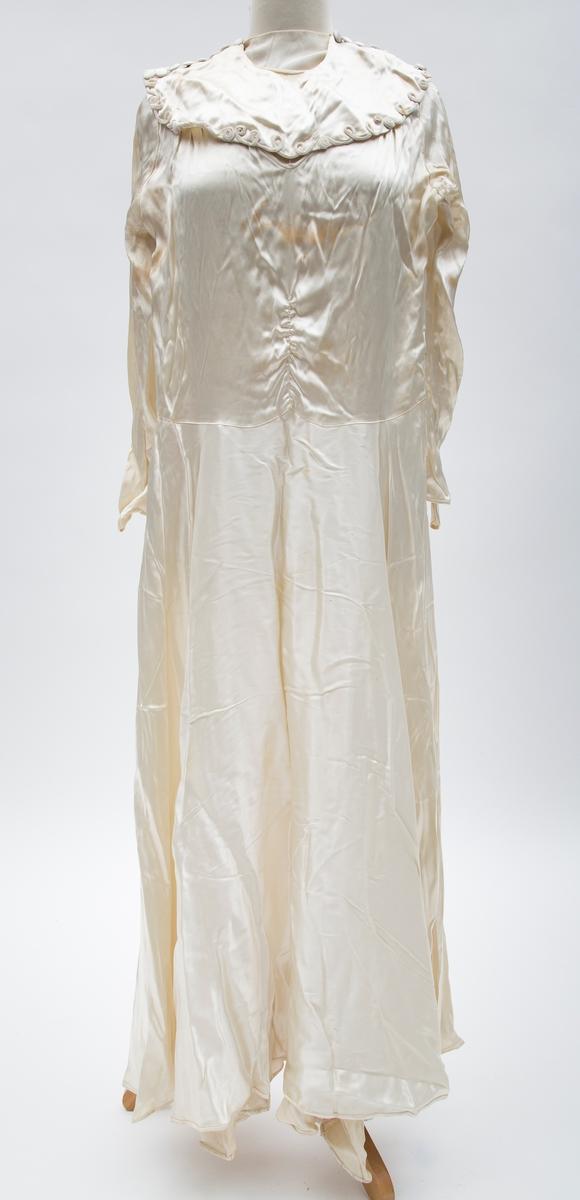 Lang brudekjole med lange ermer. Rund krage sydd på kjolen på 4 punkter. På kragen 8 silketrukne knapper over skulderen på hver side og pyntebånd langs underkanten. Åpning med trykknapper i livet på høyre side.