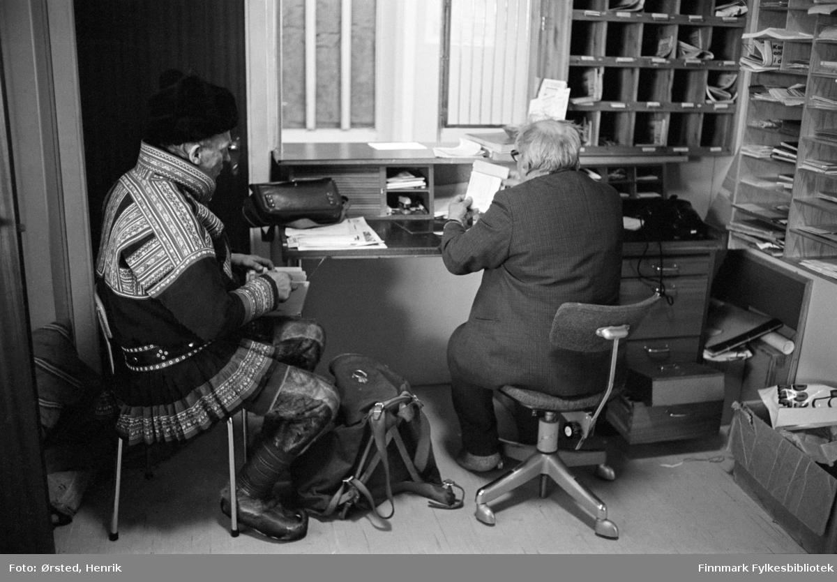 """Postfører Mathis Mathisen Buljo, bedre kjent som """"Post-Mathis"""" i samiske kretser, er ferdig med postrunden har kommet tilbake til Mierojávri poståpneri (se info under). Her sitter han på kontoret sammen med poståpner og styrer Isak Nils Mikkel Isaksen Hætta.  Fotograf Henrik Ørsteds bilder er tatt langs den 30 mil lange postruta som strakk seg fra Mieronjavre poståpneri til Náhpolsáiva, videre til Bavtajohka, innover til øvre Anárjohka nasjonalpark som grenser til Finland – og ruta dekket nærmere 30 reindriftsenheter. Ørsted fulgte «Post-Mathis», Mathis Mathisen Buljo som dekket et imponerende område med omtrent 30.000 dyr og reingjetere som stadig var ute i terrenget og i forflytning. Dette var landets lengste postrute og postlevering under krevende vær- og føreforhold var beregnet til 2 dager. Bildene gir et unikt innblikk i samisk reindriftskultur på 1970-tallet. Fotograf Henrik Ørsted har donert ca. 1800 negativer og lysbilder til Finnmark Fylkesbibliotek i 2010.  MIERONJÀVRE poståpneri, i Kautokeino herred, Finnmark fylke, under Alta postkontor, ble opprettet fra 1.4.1940 i stedet for det tidligere brevhus. Posten ble sendt med bipostruten Alta -- Kautokeino. Sirk. 10, 23.3.1940. Poststedet var grunnet krigssituasjonen evakuert fra ultimo 1944, og virksomheten ble gjenopptatt sent 1945 v/ Sirk. 31.15.11.1945. Ved etablering av nye poststedsgrupper ble poståpneriet fra 1.11.1973 benevnt underpostkontor, Sirk. 41, 31.10.1973, og fikk fra 1.1.1977 status av postkontor C, Sirk. 35, 10.12.1976. Navnet ble fra 1.1.1990 endret til MIEROJÀVRI. Sirk. 29, 31.8.1989. Postkontoret 9545 MIEROJÀVRI ble lagt ned fra 1.2.1997. Ny postadresse: 9520 KAUTOKEINO. Sirk. 1, 17.1.1997. Datostempel av 2-rings type med tverrbjelker i indre ring ble tilsendt ved opprettelsen. (9528) Poståpnere/styrere: Telefonstyrer Johan Isaksen Hætta 1.4.1940 (f.1897). Nils Isaksen Hætta 1.6.1951 (f.1913). Ellen Ragnhild Hætta 1.7.1983 (f.1956)."""