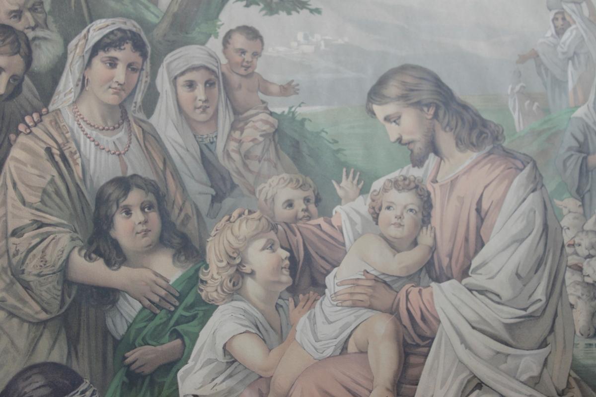 """Jesus och barnen. """"Låten barnen komma till mig"""". Jesus sitter på en stenmur och har ett barn i knäet. Flera barn har samlats kring hans fötter och även kvinnor. Längre bak står några män möjligen lärjungarna. Till höger om Jesus i bakgrunden står en herde med sin fårhjord samt två kvinnor med vattenkärl placerade på sina huvuden. I förgrunden sitter ett barn och håller ett palmblad."""