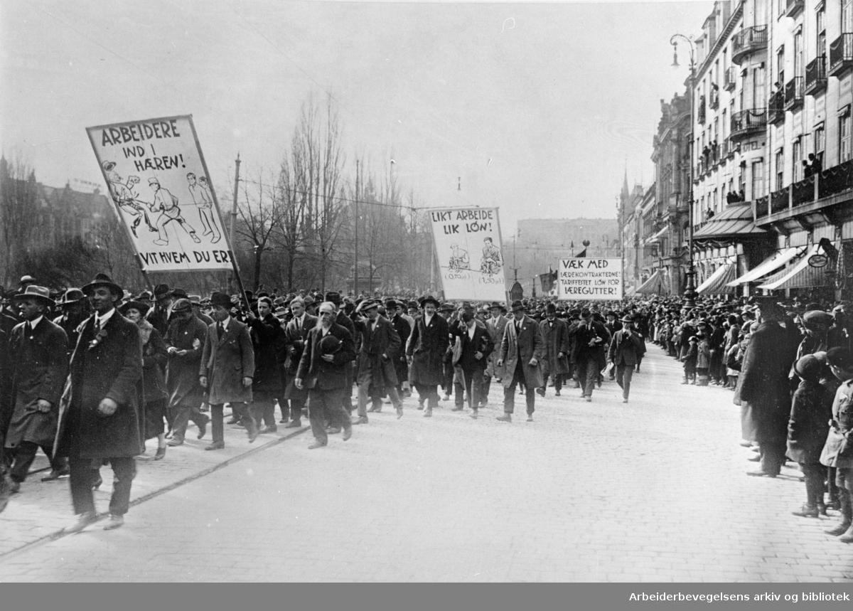 1. mai 1924 i Oslo. Medlemmer av kommunistiske ungdomslag i toget er på vei ned Karl Johans gate. Paroler: Arbeidere ind i hæren/Vit hvem du er! - Likt arbeide/Lik lønn! - Væk med lærekontraktene! Tariffestet løn for læregutter!