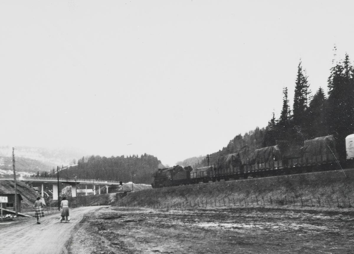 Godstog retning Trondheim kjører inn på Gudå stasjon. Toget trekkes av damplokomotiv type 63a.