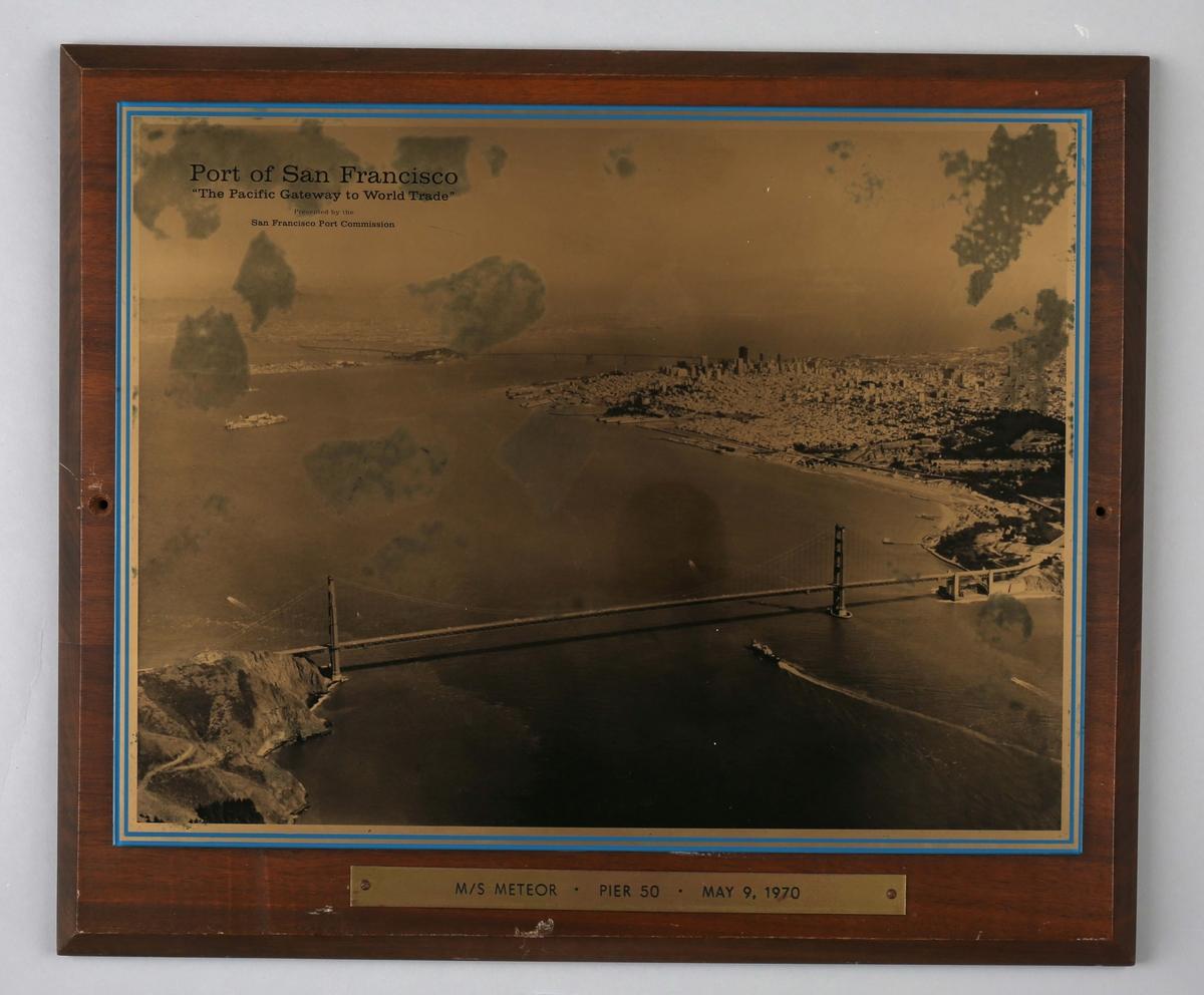 Plakett med motiv av havnen i San Francisco, USA. Flyfoto hvor en ser en stor hengebro i forgrunn.