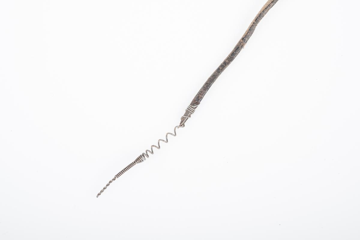 Svart venstre skinnstøvel for damer i ca. størrelse 40, 16 hulls (10 hull, 6 hekter) med lisser i skinn. I kanten rundt leggen er det en innfelt stripe i svart ull. Sålen er forsterket med mange små spikre i metall og tuppen har en kantete form.