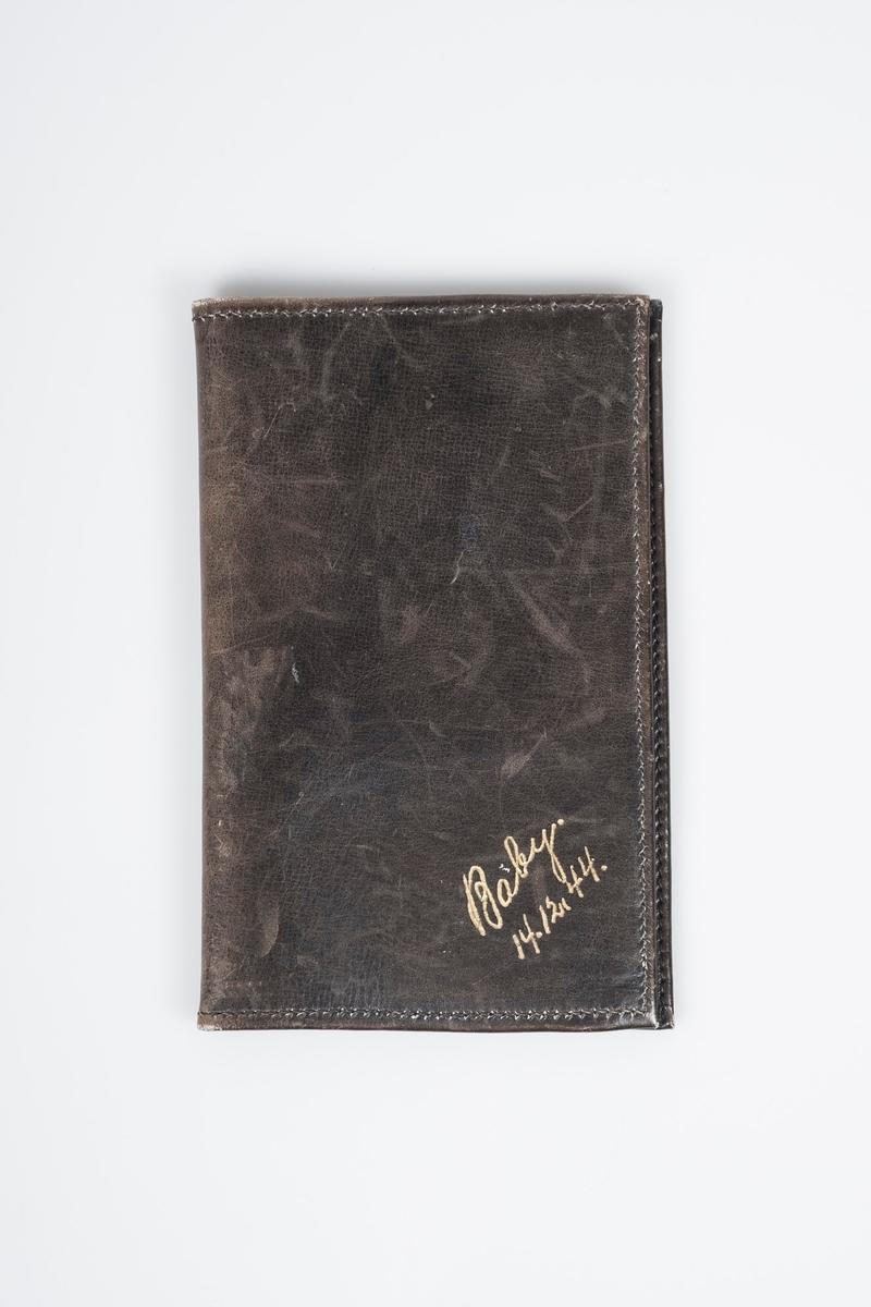 """Enkel mørkebrun lommebok i skinn. Nederst i hjørnet står det i gyldne bokstaver: """"Baby 14.12.44."""" På innsiden to hovedlommer, den ene med lukking med stropp, den andre åpen med to mindre lommer påsydd."""