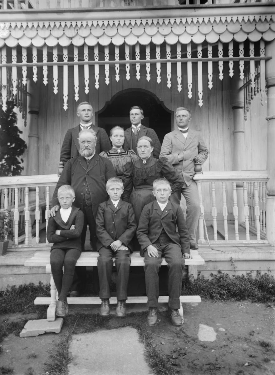 Antatt familiebilde med 9 personer og to generasjoner. Foreldre, 1 datter og 6 sønner. Meget særpreget inngangsparti til hvitmalt bygning.