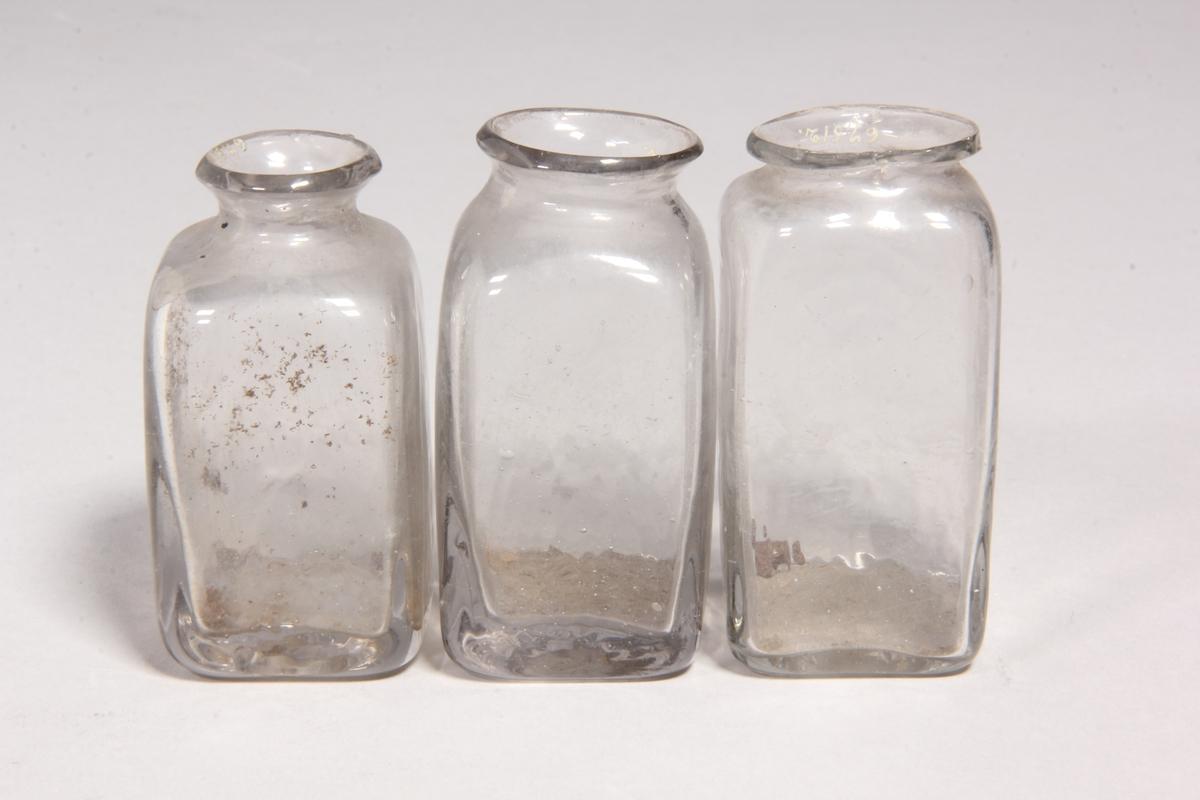 Burkar, 3 st, av klart glas. Fyrkantiga med kort hals och utvikt mynning.