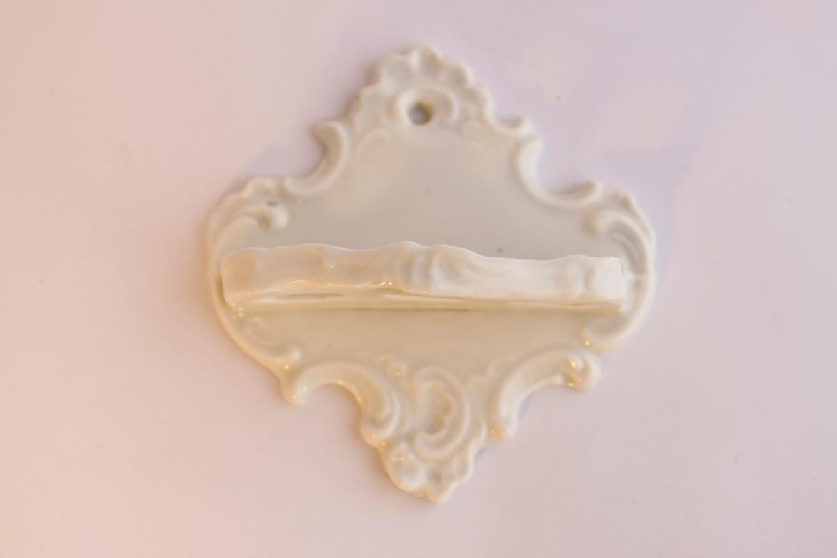 Tandborsthållare i vitt porslin, som ska hängas upp på väggen, med plats för tre tandborstar.