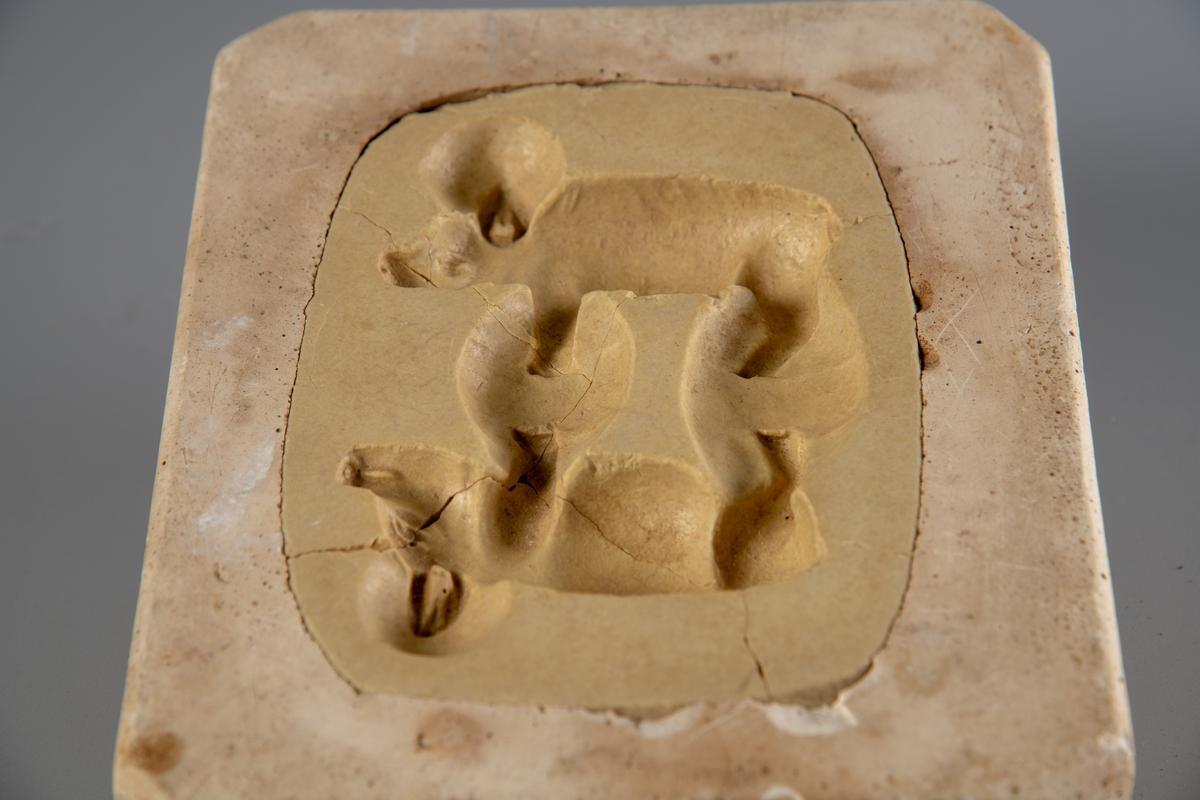 Rektangulær gipsform med avrundete hjørner. Formmotivet er to halve griser, som til sammen blir en marsipangris. Grisen er 9 cm lang på sitt lengste. Formen er litt knust i midten, men bitene sitter fast,