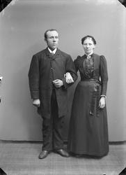 Par med dame i mørk drakt og krans i håret og mann i mørk dr