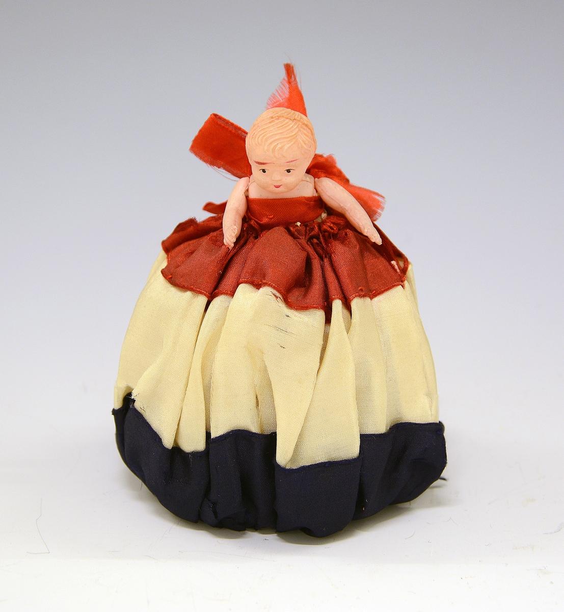Dukke med stort skjørt i rødt, hvitt og blått. Dukken i plast.