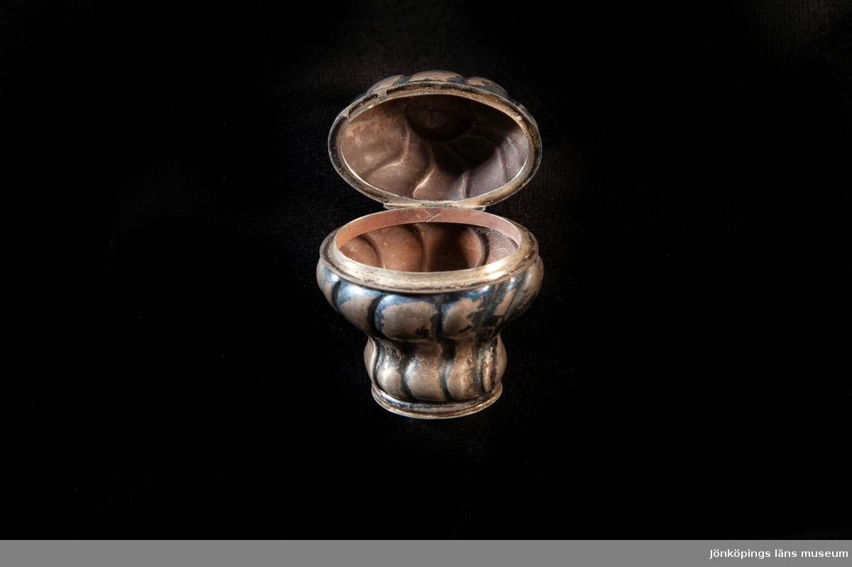 """En hög dosa av silver i rokoko. Dekorerad med s.k. """"knäckta åsar"""" i relief ochhögst upp på locket en genombruten krona. Överst på kronan finns en infattad röd sten av glas.Utländska stämplar i botten.Troligen dansk tillverkning.Jfr JM 18 742."""