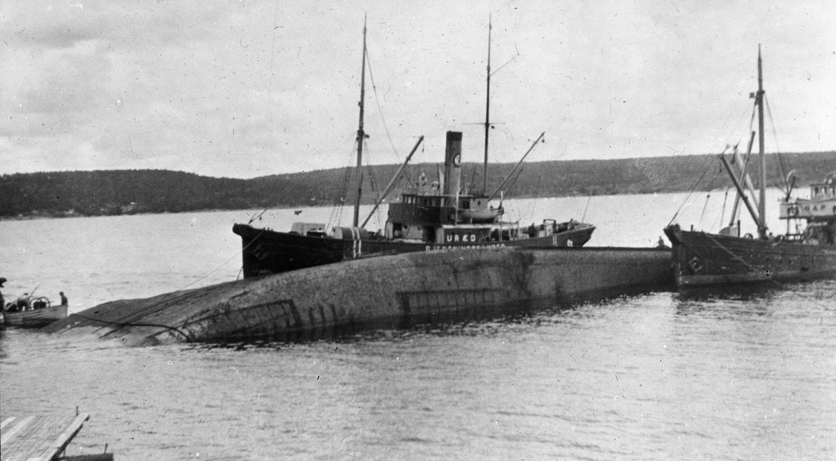 Ukjent havarert fartøy, hele langsiden av skipet ligger under vann. Bjergningsdamper URÆD og RAP, samt en robåt med dykker pumpe ved skipet.