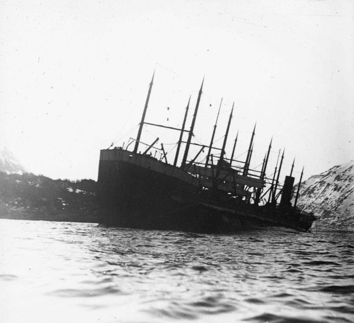 Havarert motorskip i en fjord, under opphugging.