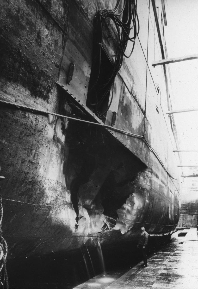 Skipsskrog i tørrdokk. Skroget har flerre i siden.