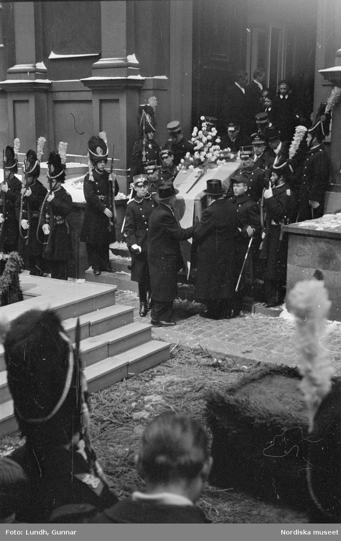 Troligen begravningen av Prins Gustaf Adolf, en kista bärs ut från Storkyrkan, kungafamiljen går ut från Storkyrkan, militärer i uniform står i givakt, kistan står på en katafalk som dras av hästar, en folksamling står längs vägen när begravningsföljet passerar.