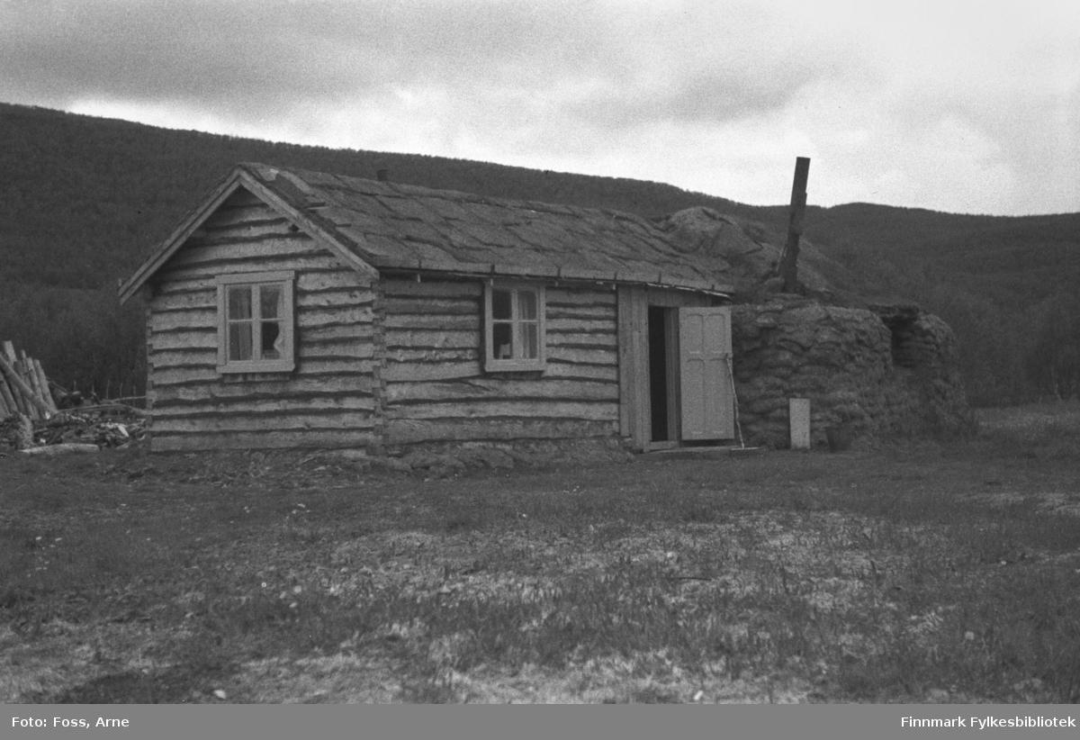 Et tømmerhus med fjøs  i andre enden. Fjøsdelen er bygget av torv på samme vis som gammer ble bygd i Finnmark. Slike midlertidige kombinasjonshus var det mange av inntil gjenreisningen var ferdig, og mange av disse stod i mange år etter krigen.