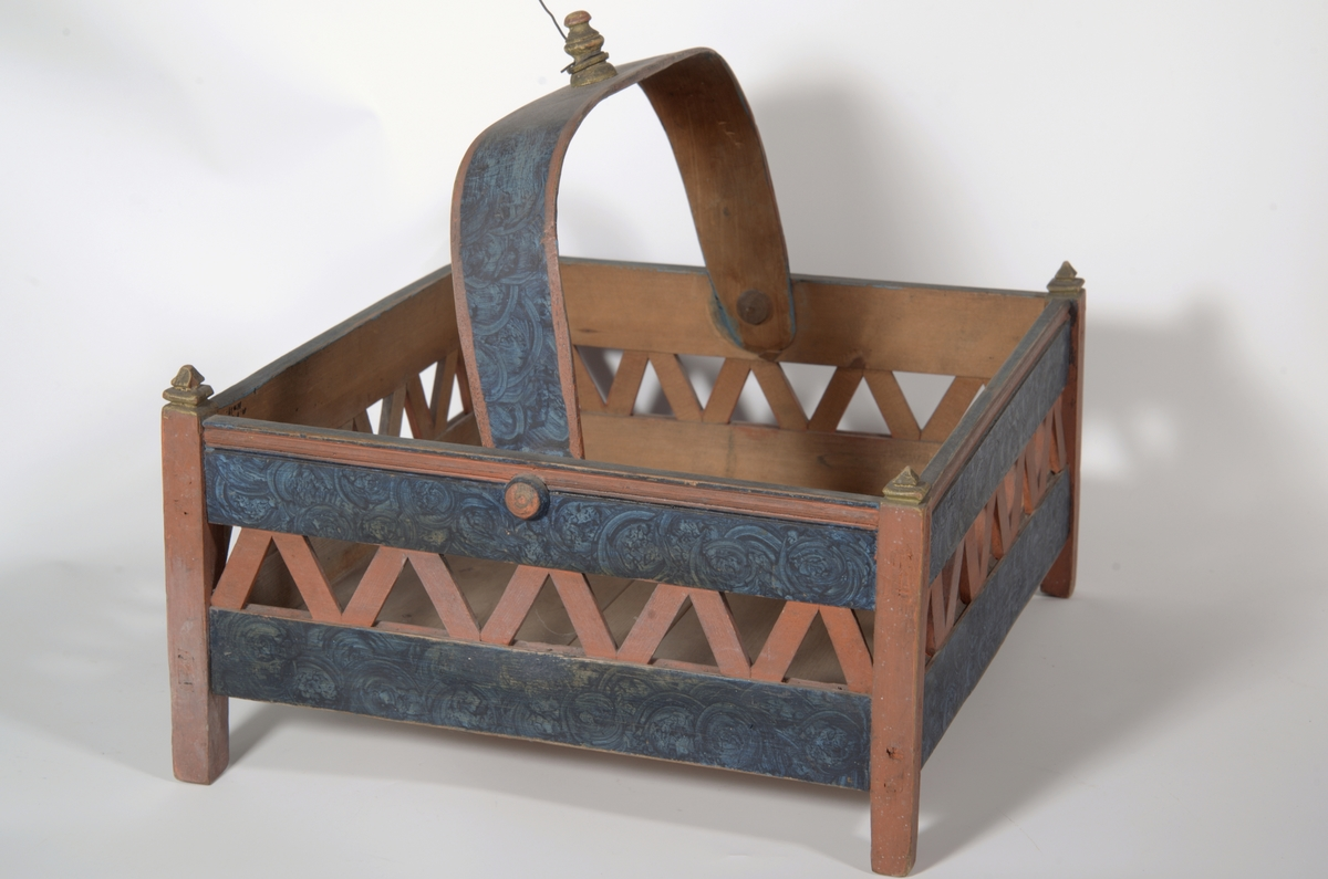 Rektangulær bunn, hjørnestolper m/rammer oppe og nede, mellom rammene fliser i siksakmønster, hank  til å legge ned.