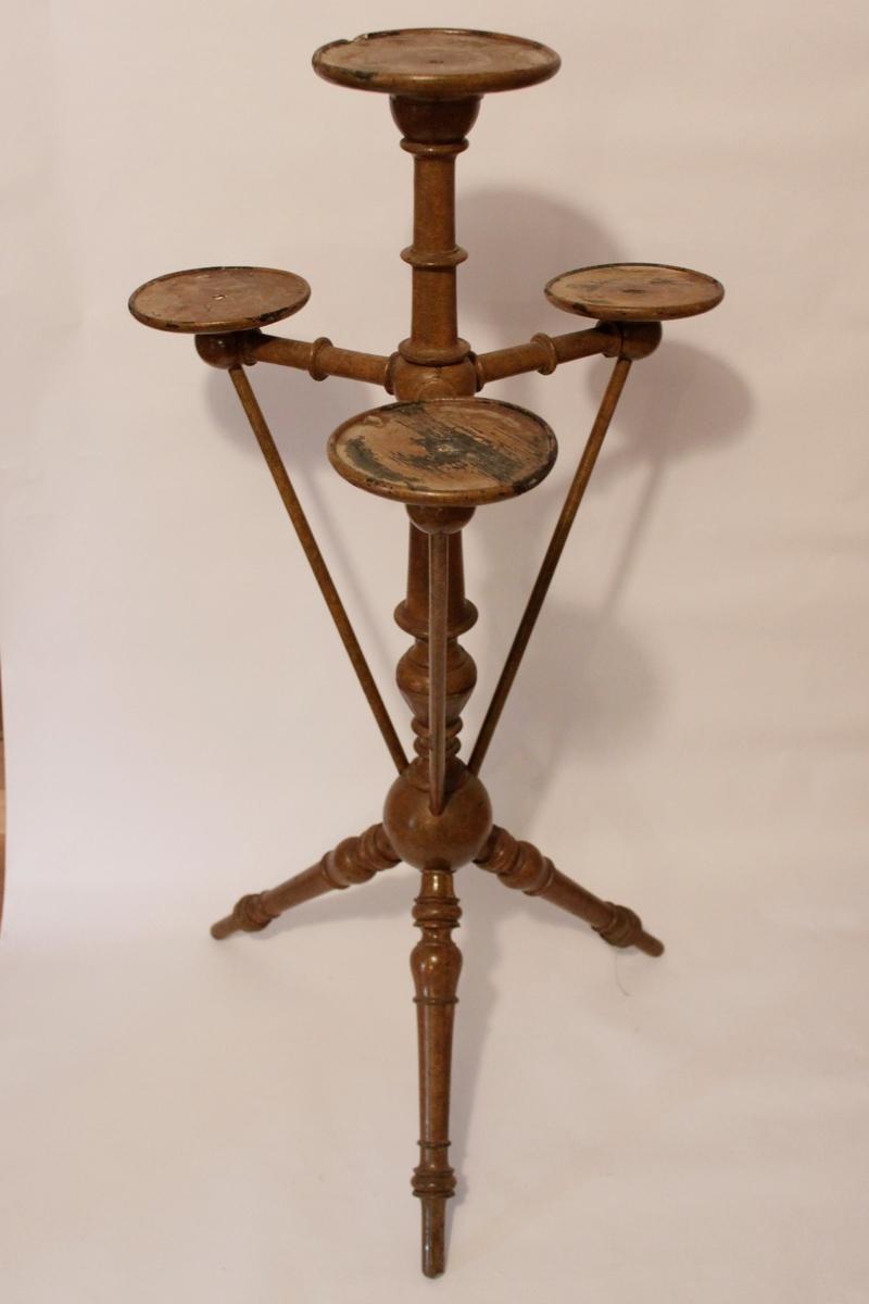 Piedestal med plats för fyra krukor. En högst upp i mitten och tre en bit ner runt den mittersta. Piedestalen har formen av en pelare som delar sig i tre snedställda svarvade ben nedtill.