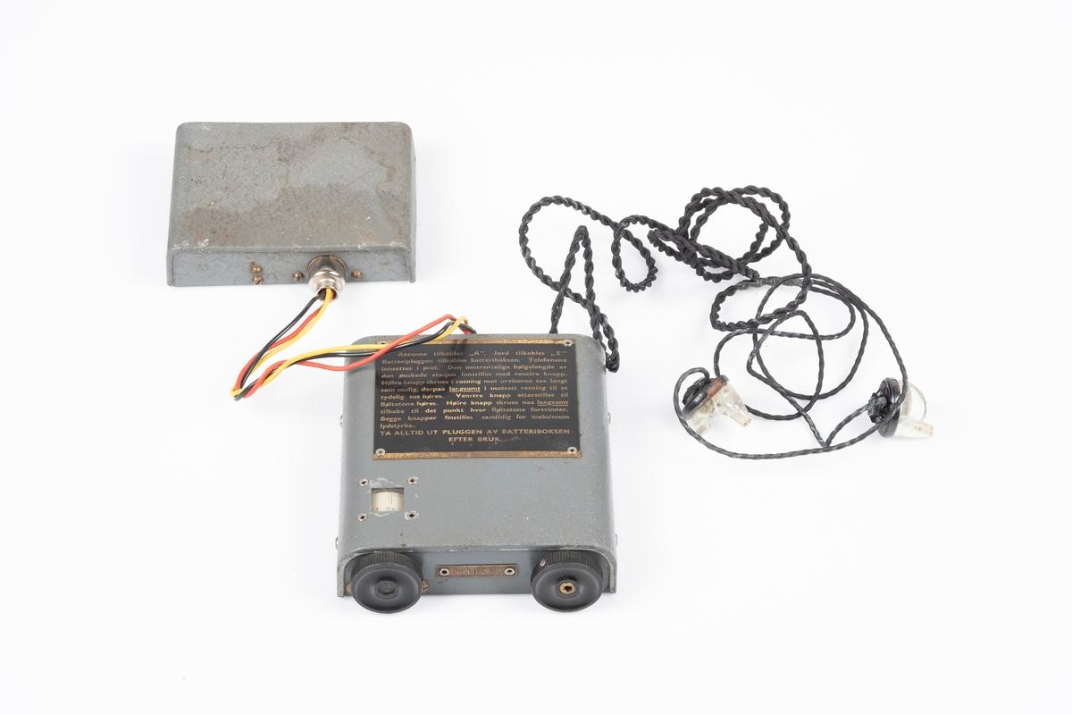En kortbølgeradio i 3 deler; radio, tørrbatteri og ørepropper. Radioen og batteriets ytterplater er av metall som er lakkert i grått. Radioen har to svarte vriknapper. Det er et lite vindue ved den ene vriknappen som viser frekvensen. På baksiden er det ledning som kobles til batteriet. Det er to hull til plugger og en kontakt for øreproppene. Det er påfestet en plate med instrukser på på oversiden. Mellom vriknappene er det påfestet en liten plate med modellnummer. Øreproppene har propper i plast som kan fjernes fra ledningen.  Ifølge instruksen så skal det også følge med antenne og jord, men som mangler her.