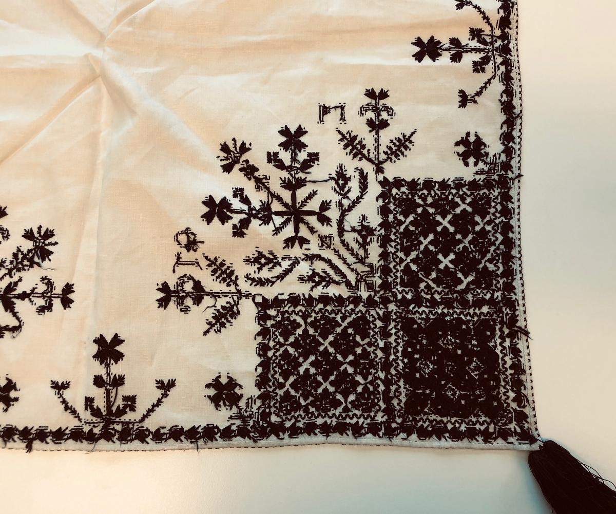 Blomsterinspirerat mönster i kvadrater i hörnen. Blomsterliknande bård omkring kvadraterna och längs två långsidor. Mellan ryggsnibb och framsnibb blomsterkorg. Istället för majstångsspira finns en stor blomsterdekoration.