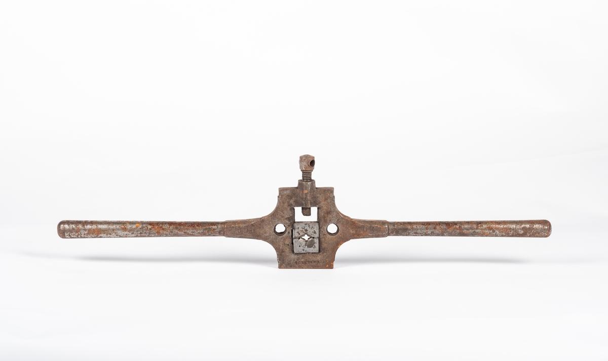 Verktøyet har to like lange håndtak på hver side. Skrustikken står ut til siden på midten. Bakkeholderen er firkantet, gjengebakken har oval form.