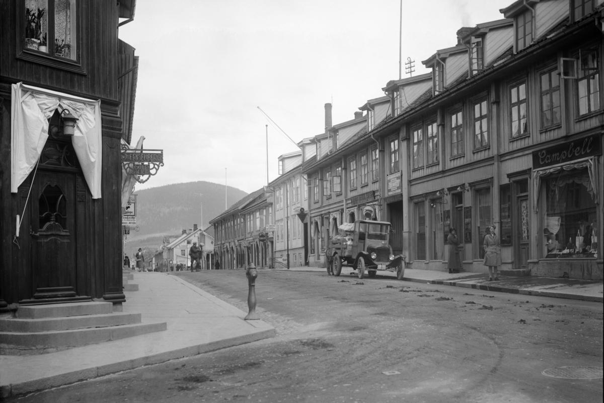 Storgata, Lillehammer. Frisenberg-hjørnet med Hellebergs forretning på østsiden. Lastebil D-140 parkert utenfor Helleberg
